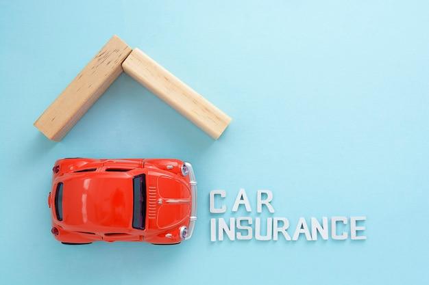 Modello di auto rossa di parole di assicurazione auto e tetto in legno su sfondo blu