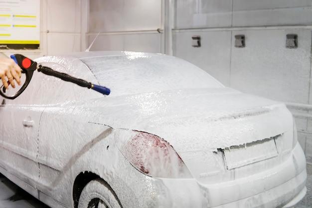 L'auto è ricoperta di schiuma per lavare l'auto al chiuso. autolavaggio automatico. shampoo per auto. vista laterale del processo di pulizia, vista posteriore. self-service, insaponatura