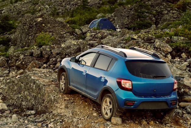 L'auto è parcheggiata tra le rocce in primo piano la tenda sullo sfondo è visibile