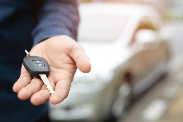 Chiave della macchina, uomo d'affari che consegna dà la chiave della macchina all'altro uomo sullo sfondo dell'auto.