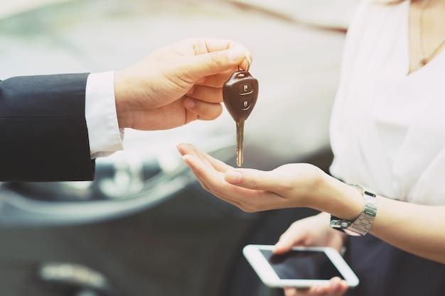 Chiave della macchina, uomo d'affari che consegna dà la chiave dell'auto all'altro uomo in macchina