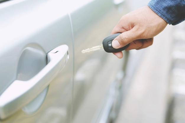 Chiave della macchina, uomo d'affari che consegna dà la chiave dell'auto all'altra donna sullo sfondo dell'auto.