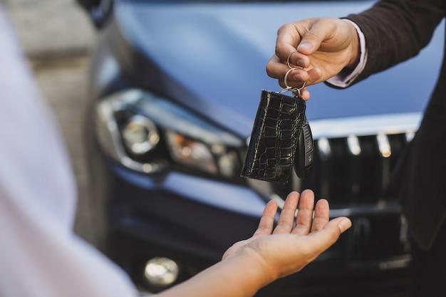 Consegna delle chiavi dell'auto dal venditore di auto al cliente