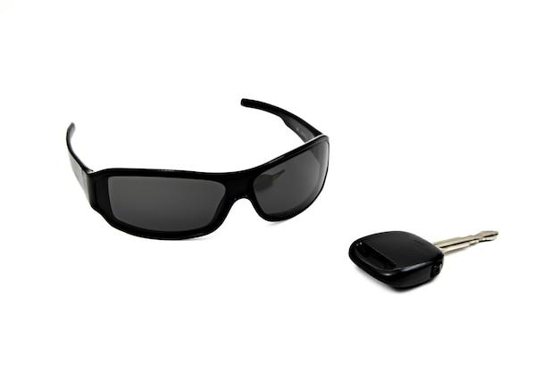 Chiave della macchina e occhiali da sole su sfondo bianco isolato