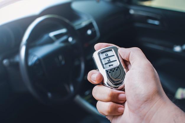 Telecomando per l'ingresso senza chiave dell'auto in una mano dell'auto del proprietario con sfondo sfocato dell'interno dell'auto