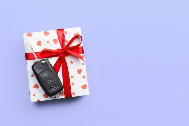Chiavi della macchina sulla confezione regalo con cuori di carta da imballaggio
