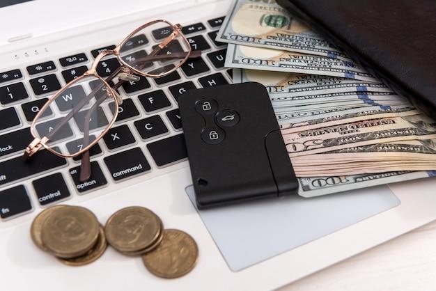Chiavi della macchina con banconote da un dollaro sulla tastiera del computer portatile, concetto di vendita