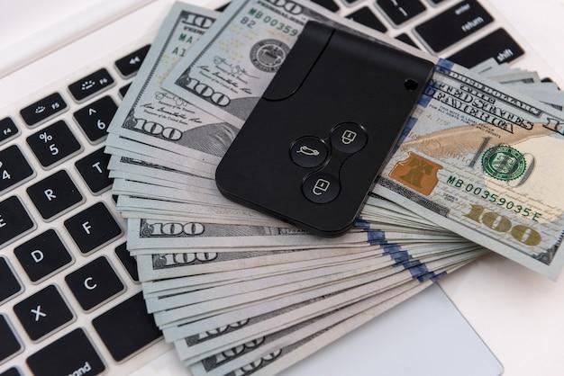 Chiavi della macchina con banconote da un dollaro sulla tastiera del laptop, concetto di vendita sale