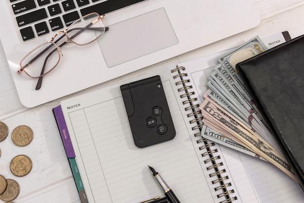 Chiavi della macchina con banconote da un dollaro sulla tastiera del laptop, concetto di vendita