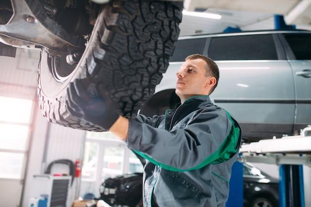 Auto sollevata in servizio automobilistico per il fissaggio, il lavoratore ripara la ruota