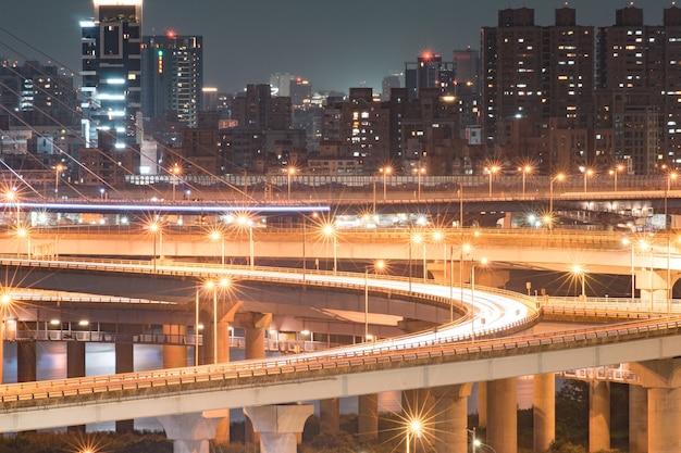 Sentieri luminosi per auto del nuovo ponte di taipei - ponte occupato di taipei dopo l'orario di lavoro