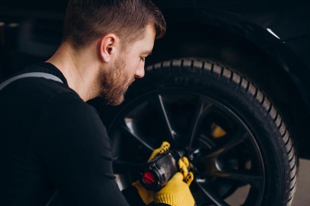 Meccanico di automobile che cambia le ruote in automobile