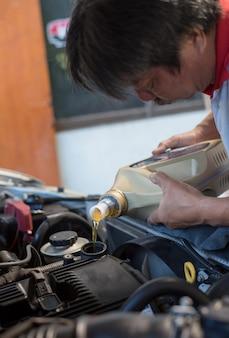 Il meccanico di automobile riempie un olio motore lubrificante fresco