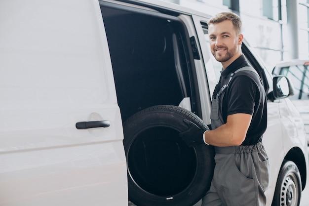 Meccanico di automobile che tiene le gomme nuove vicino al furgone bianco