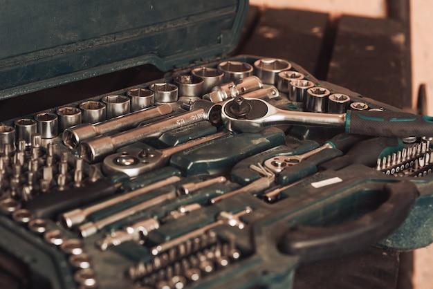 Il meccanico tiene in mano una chiave inglese e passaggi sullo sfondo di una tavola con strumenti per riparare l'auto. avvicinamento. autofficina per riparazioni auto