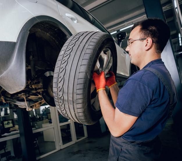 Meccanico di automobile che ispeziona dettaglio della ruota e della sospensione dell'automobile sollevata al distributore di benzina di riparazione