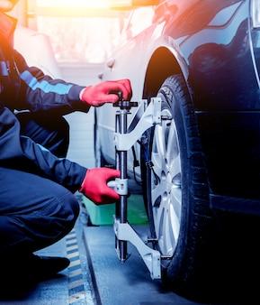 Meccanico di automobile che installa sensore durante la regolazione delle sospensioni.