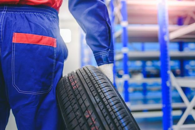 Il meccanico automobilistico sta cambiando le nuove gomme in stock per cambiarle per i clienti in garage - cambiando ruote / pneumatici.