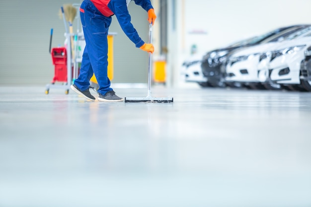 Pulizia del centro di assistenza del meccanico automobilistico con mop per far rotolare l'acqua dal pavimento epossidico. nel centro servizi di riparazione auto.