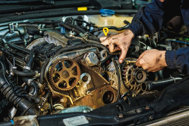 Meccanico di automobile che ripara un motore. meccanico che lavora al motore di un'auto. officina meccanica.