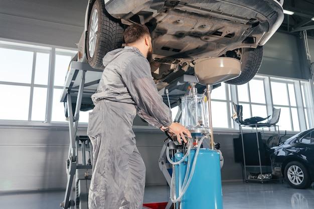 Meccanico di automobile che sostituisce l'olio nel motore del motore. negozio di servizi auto