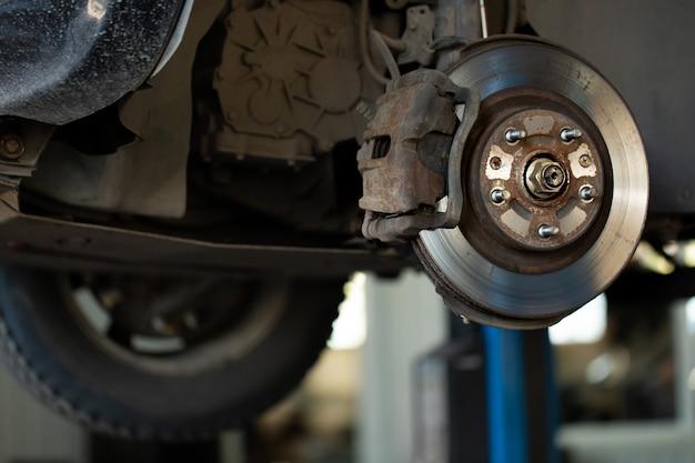 Lavoratore del meccanico di automobile che ripara sospensione dell'automobile sollevata alla stazione automatica del negozio del garage di riparazione