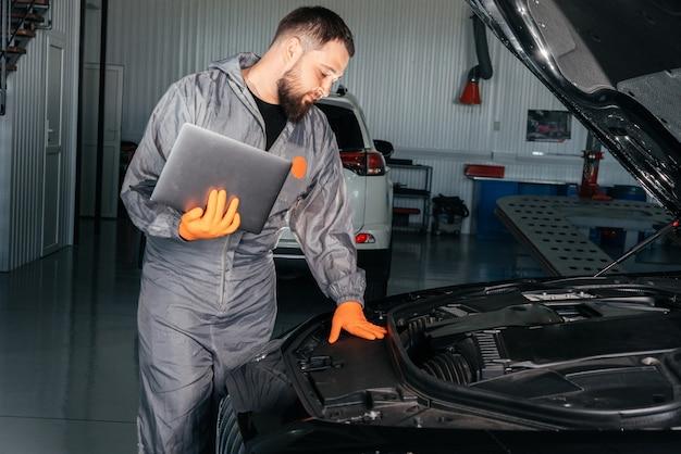 Meccanico di automobile che lavora con un computer portatile nel servizio di riparazione automatica che controlla il motore dell'automobile