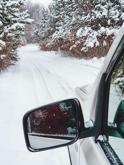 Specchio per auto davanti con vista del sentiero innevato nello spazio della copia della foresta