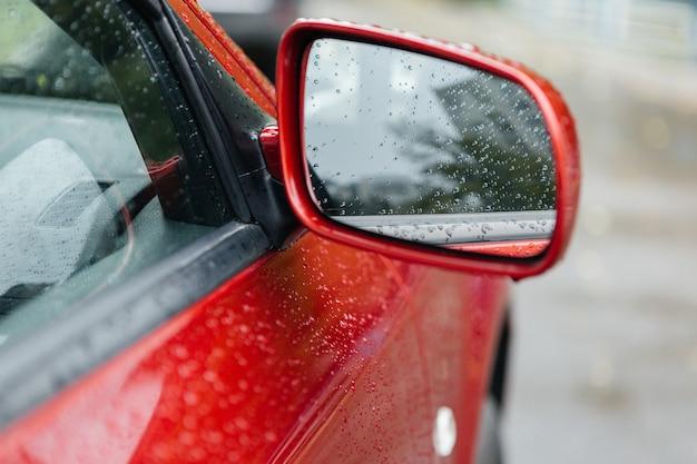 Specchio per auto con gocce di pioggia. auto rossa