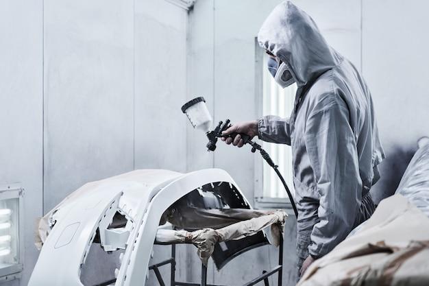 Servizio di verniciatura e riparazione auto. il meccanico in tuta bianca dipinge l'auto con il polverizzatore dell'aerografo nella camera di verniciatura