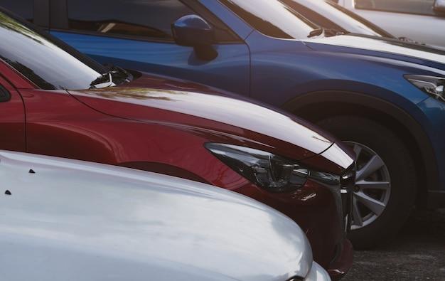 Auto parcheggiata nel parcheggio dell'aeroporto per il noleggio vista laterale dell'auto suv blu rossa auto di lusso usata