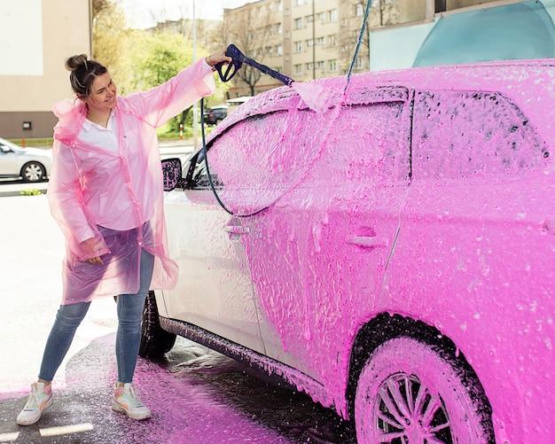 Auto in gommapiuma rosa all'autolavaggio, una donna lava felicemente la sua auto