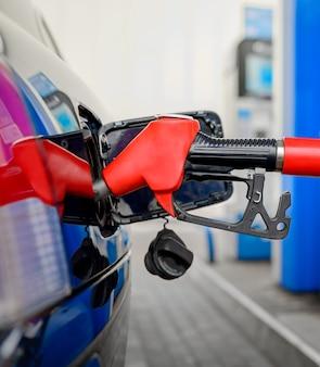 Rifornimento di carburante su una stazione di servizio con il primo piano rosso dell'ugello della pompa del carburante