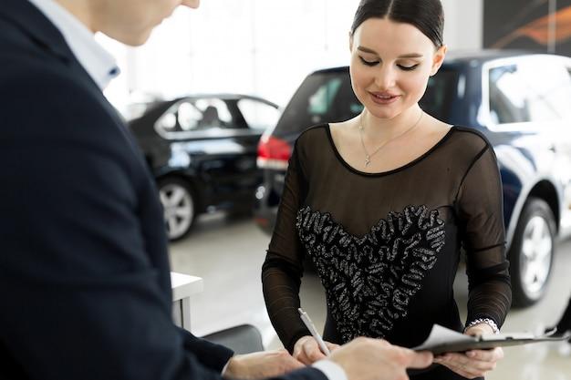 Concetto di noleggio auto e assicurazione, giovane commesso che riceve denaro e consegna la chiave dell'auto al cliente dopo aver firmato un contratto di accordo con un buon affare approvato per affitto o acquisto.