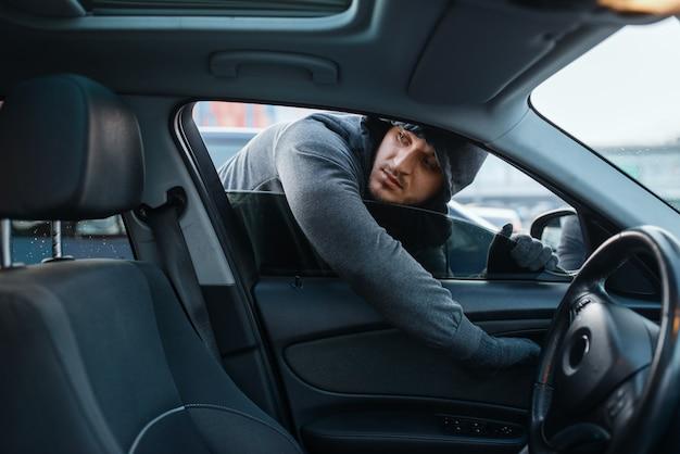 Rapinatore di automobili che apre la porta, rischia il lavoro, ruba. bandito maschio incappucciato entra nel veicolo in parcheggio. rapina automobilistica, crimine automobilistico