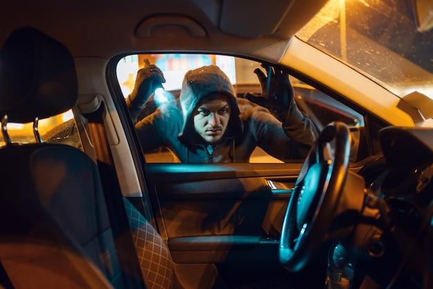 Rapinatore di auto con torcia in cerca di merci, stile di vita criminale, furto.