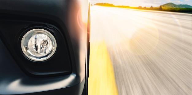 Macchina che corre sulla strada asfaltata con un bagliore di luce solare