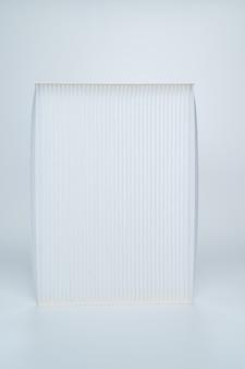 Il filtro dell'aria dell'auto su uno sfondo bianco. negozio di ricambi per auto. riparazioni e manutenzioni auto.