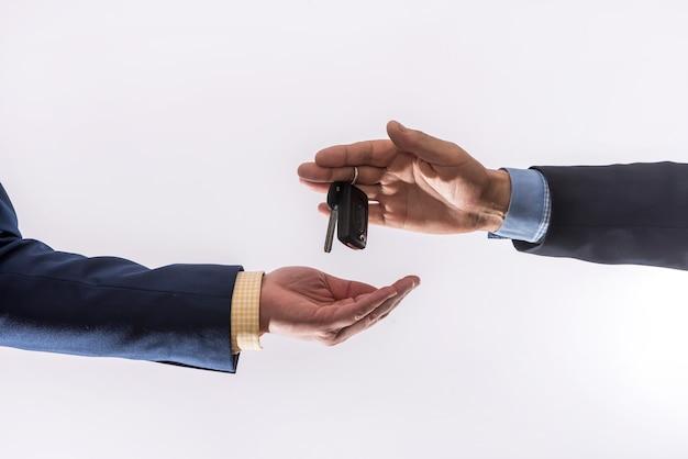 Vendite di auto in condizioni di quarantena coronavirus mani che tengono la chiave dell'auto e banconote da un dollaro isolate. acquisto del concetto di auto
