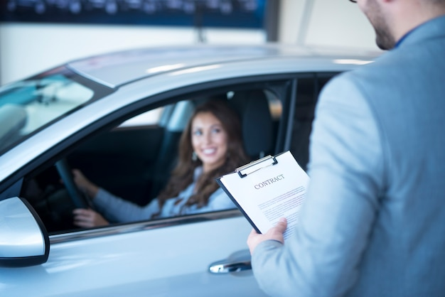 Venditore di auto con contratto in attesa di auto nuova di zecca mentre il cliente seduto all'interno di un veicolo nuovo.