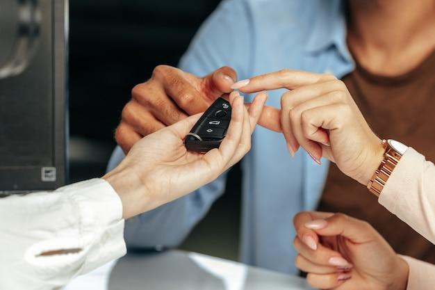 Venditore di auto che dà le chiavi a un cliente da vicino