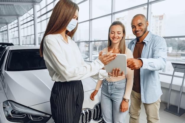 La commessa di auto che indossa la mascherina medica mostra che gli acquirenti accoppiano qualcosa sulla tavoletta digitale. .nuovo concetto di requisiti di lavoro pandemici