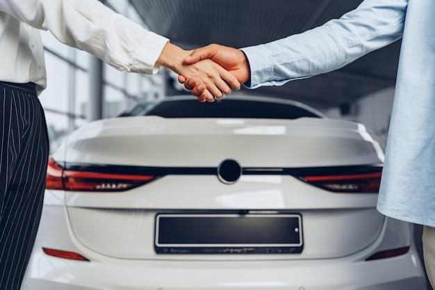 Stretta di mano del venditore e dell'acquirente di auto presso la concessionaria di auto su uno sfondo di auto nuove