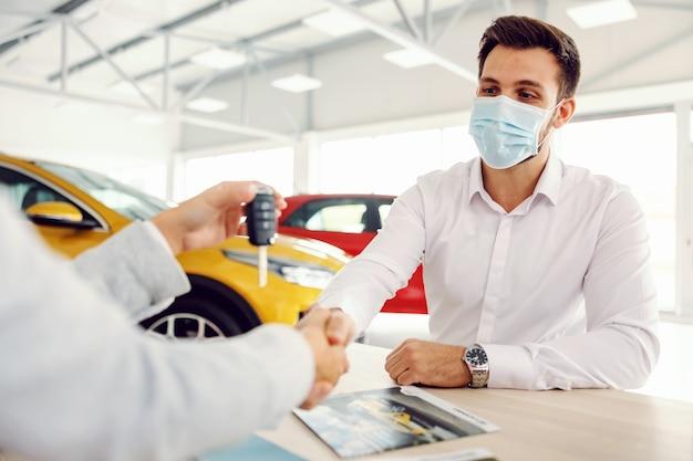 Venditore di auto stringe la mano al cliente e gli consegna le chiavi della macchina mentre è seduto nel salone dell'auto durante il virus corona