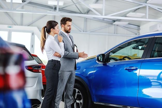 Venditore di auto che mostra al cliente un'auto nuova di zecca e parla delle sue prestazioni.