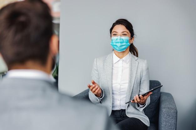 Venditore di auto seduto con un cliente nel salone dell'auto e parlando di promozioni. epidemia di coronavirus.