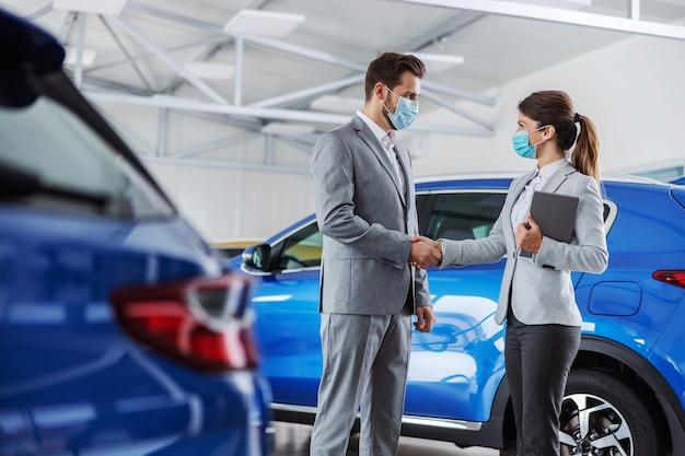 Venditore di auto in piedi nel salone dell'auto con un cliente e che gli stringe la mano. hanno fatto un accordo. entrambi hanno maschere per il viso perché è l'epidemia di virus corona.