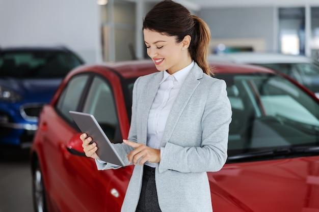 Venditore di auto in tuta in piedi nel salone dell'auto e utilizzo di tablet per la scelta dell'auto giusta.