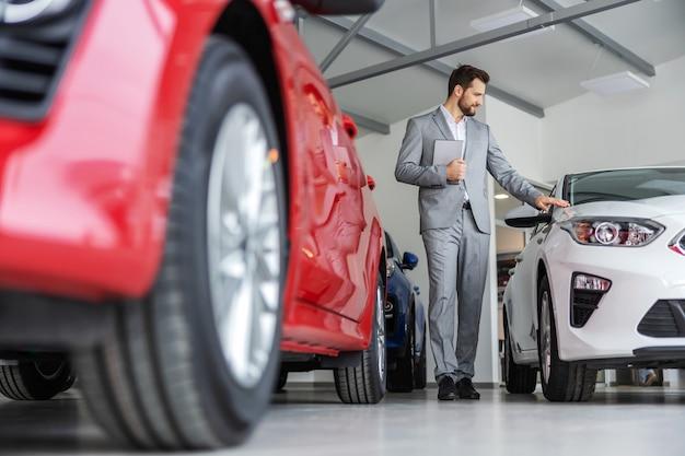 Venditore di auto che cammina intorno al salone dell'auto e che tiene compressa. ci sono molte nuove auto pronte per essere vendute.
