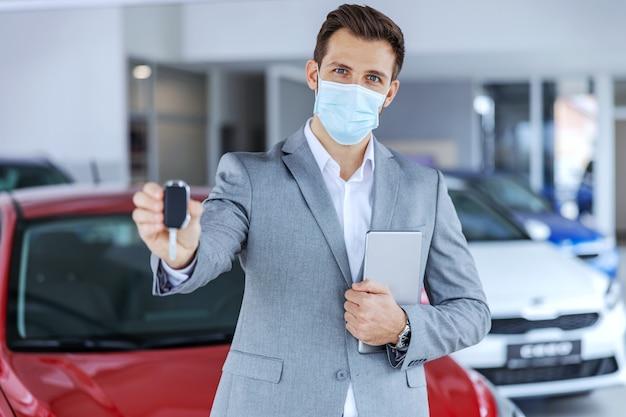 Venditore di auto con maschera facciale in piedi nel salone dell'auto e mostrando le chiavi su una nuova auto di marca che sono pronte per essere vendute
